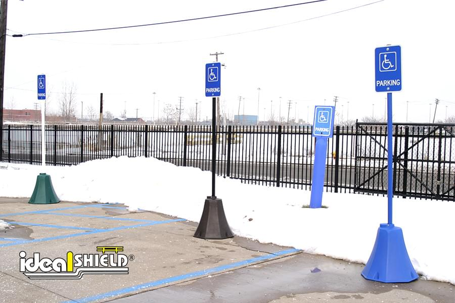 Ideal Shield's Green, Black, & Blue Handicap Accessible Octagon Sign Bases in a parking lot