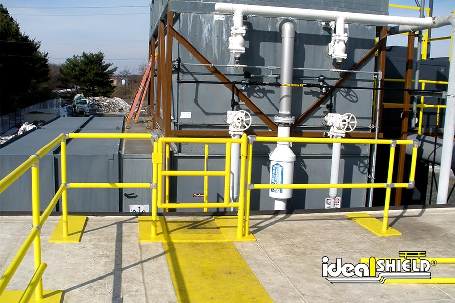 Ideal Shield's pipe & plastic roof fall protection railing with base plates and a custom gate
