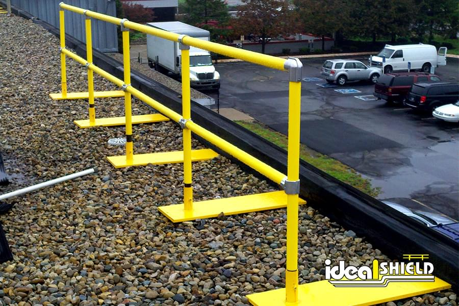 Ideal Shield's pipe & plastic roof fall protection railing with base plates on gravel rooftop