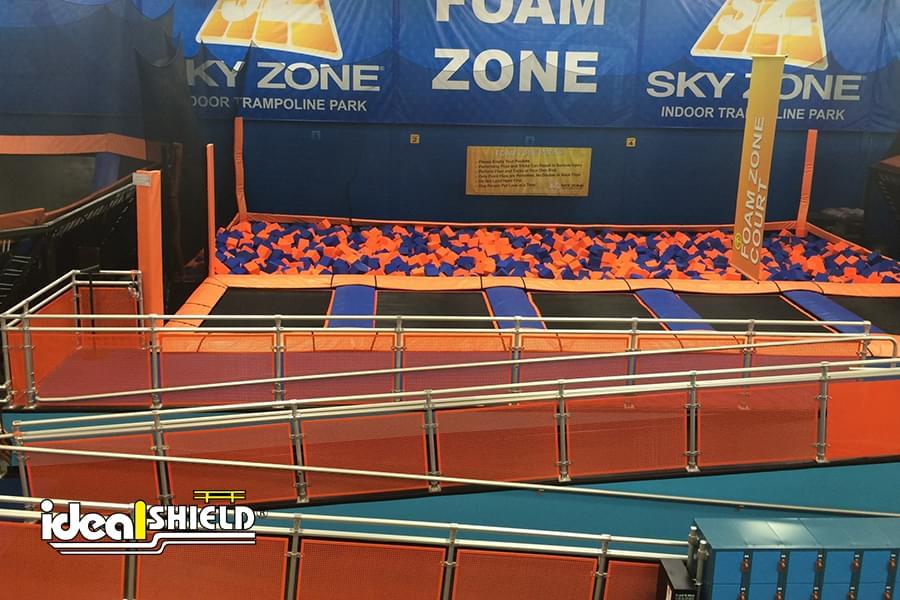 Ideal Shield's custom made Aluminum Handrail with orange infill panels at SkyZone