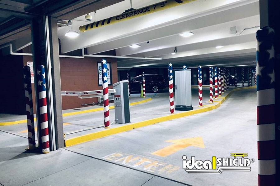 Ideal Shield's American Flag Fabric Bollard Covers lining a parking garage entrance