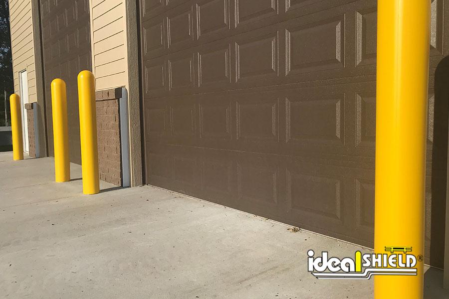 "Ideal Shield's yellow 1/8"" Bollard Covers guarding garage doors"