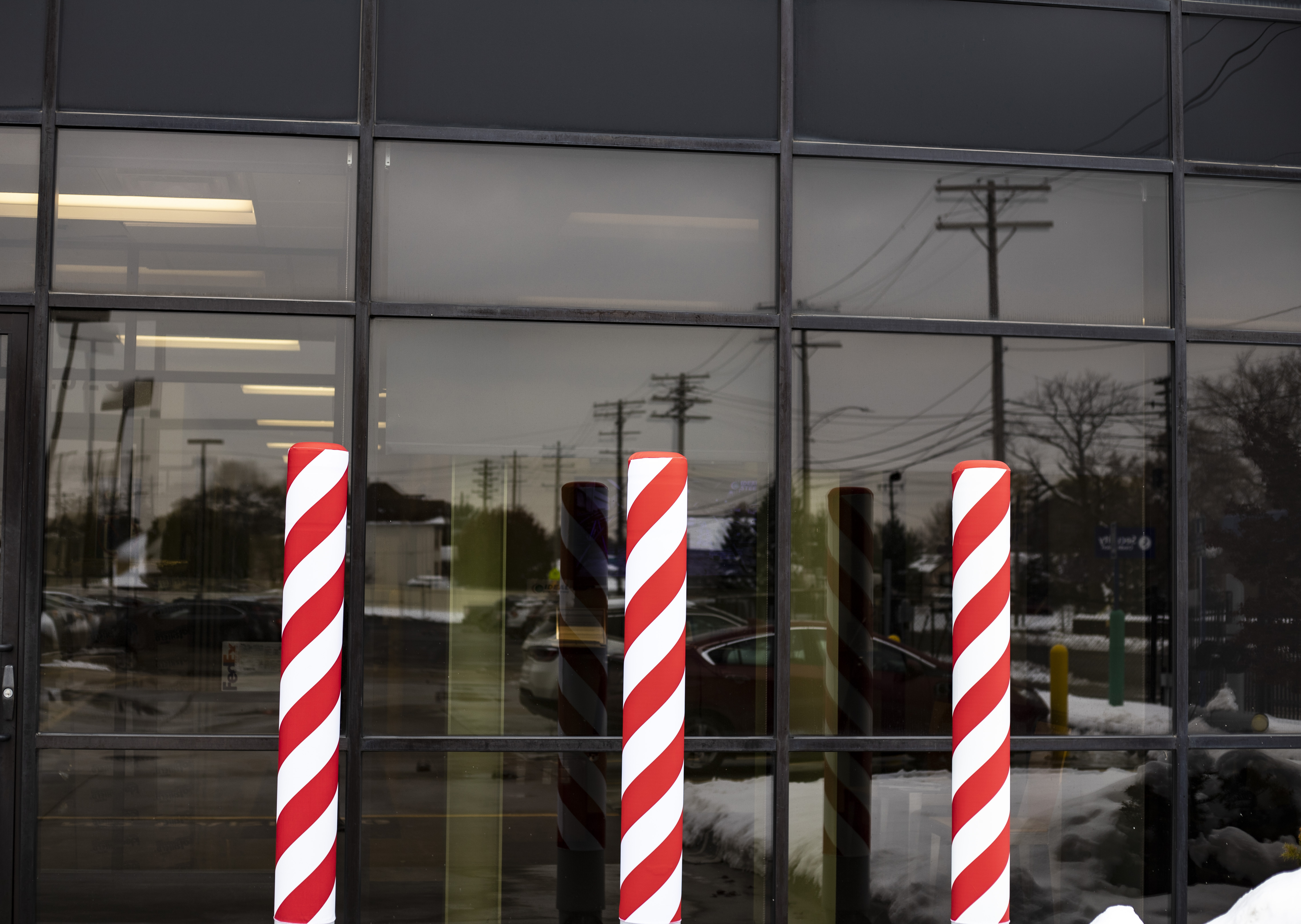 Ideal Shield's Candy Cane AdShield Fabric Bollard Covers over Flat Top Bollard Covers