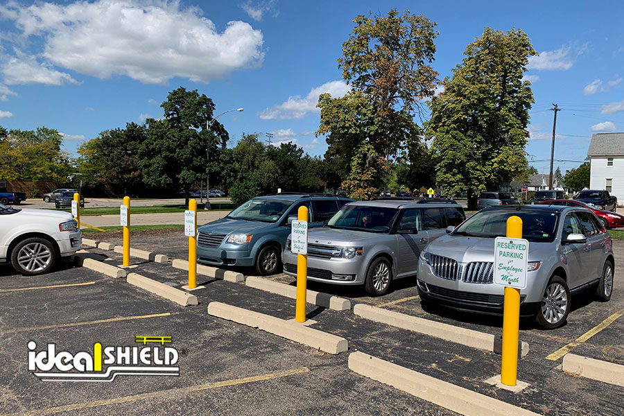 """Ideal Shield's four-inch 1/4"""" Bollard Covers with signage in a dentist's office parking lot"""