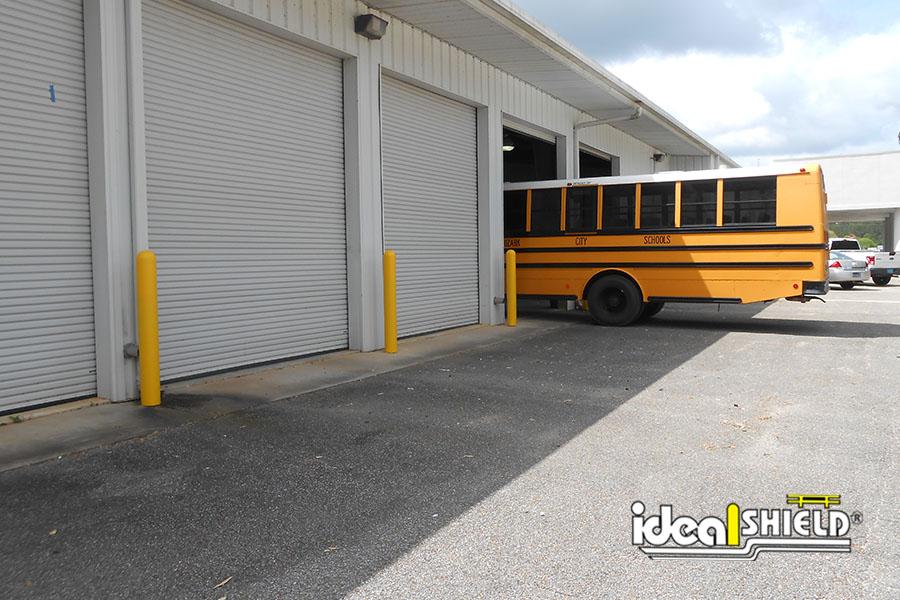 "Ideal Shield's 1/8"" Bollards Covers guarding a school bus maintenance facility"