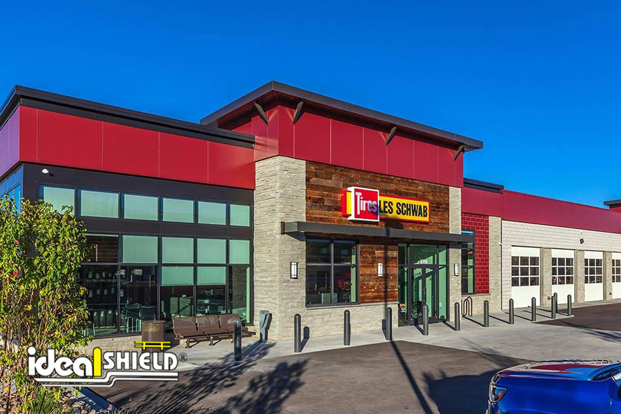 """Ideal Shield's gray 1/4"""" Bollard Covers guarding the storefront at Les Schwab"""