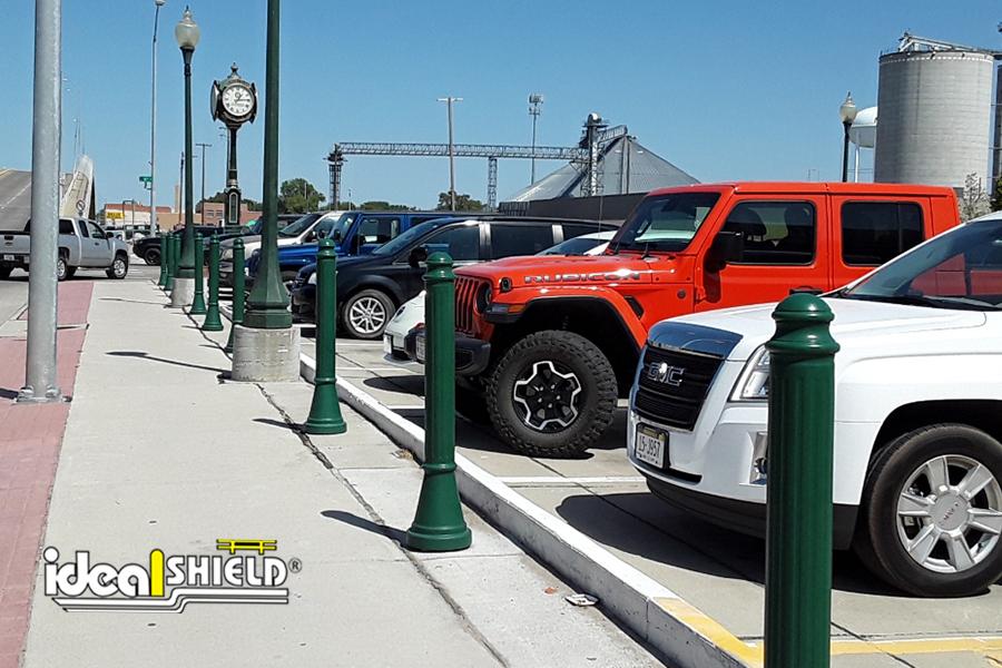 "Ideal Shield's 4"" Paramount Decorative Bollard Covers lining a sidewalk"