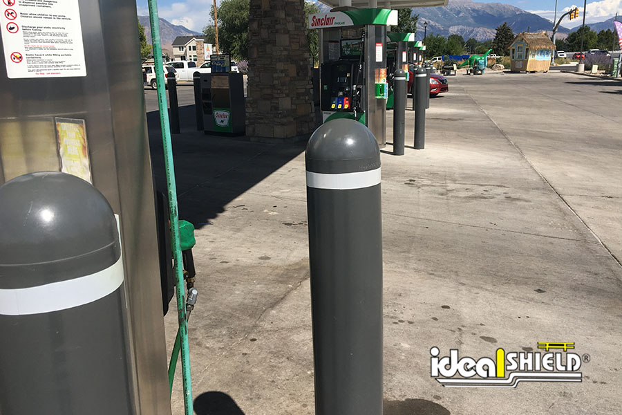 """Ideal Shield's gray 1/4"""" Bollard Covers with white reflective tape at Sinclair gas station"""