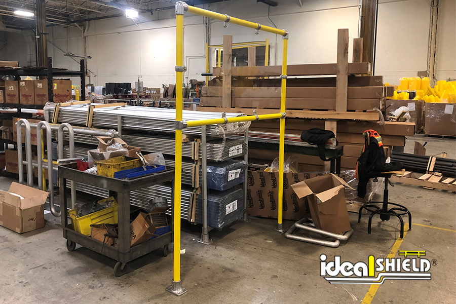 Ideal Shield's Stand Up Sneeze Guard in Steel Pipe & Plastic on a manufacturing floor