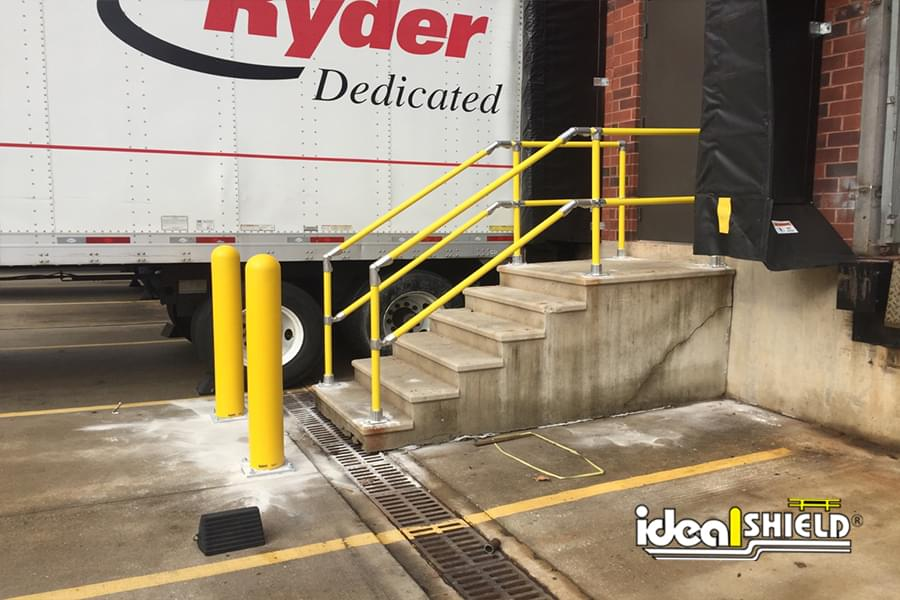 """Ideal Shield's yellow plastic 1/8"""" Bollard Covers guarding a stairway with Steel Pipe and Plastic handrail"""