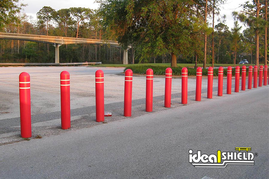 """Ideal Shield's Red Plastic 1/8"""" Bollard Covers with Reflective Tape Stripes at Disney World Parking Lot"""