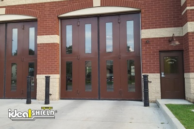 Ideal Shield's black Metro Decorative Bollard Cover at a fire station protecting garage doors