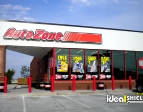 "Ideal Shield's red 1/4"" Bollard Cover guarding an AutoZone storefront and sidewalk"