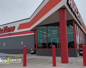 "Ideal Shield's 1/4"" Red Bollard Covers guarding an AutoZone storefront"