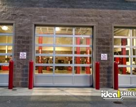 "Ideal Shield's red 1/4"" Bollard Cover guarding garage doors at Costco"