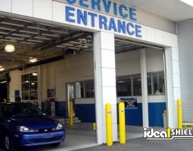 "Ideal Shield's yellow 1/4"" Bollard Covers guarding garage door ways at a car dealership"