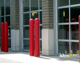 "Ideal Shield's red 1/4"" Bollard Cover guarding a car dealership's garage doors"
