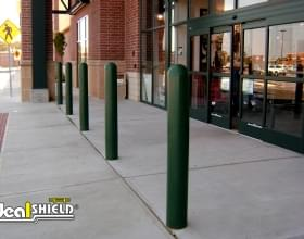 "Ideal Shield's green 1/4"" Bollard Cover guarding Dick Sporting Good's storefront"