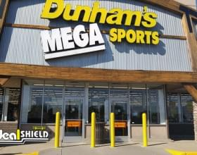 "Ideal Shield's yellow 1/4"" Bollard Covers guarding the storefront at Dunham's Mega Sports"