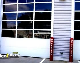 "Ideal Shield's red 1/4"" Bollard Cover guarding Jiffy Lube garage doors"