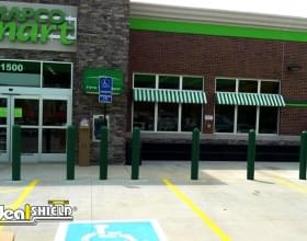 "Ideal Shield's green 1/4"" Bollard Cover guarding MapCo Market's storefront"