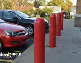 "Ideal Shield's red 8"" plastic dome top Bollard Covers used for storefront protection at O'Reilly Auto Parts"