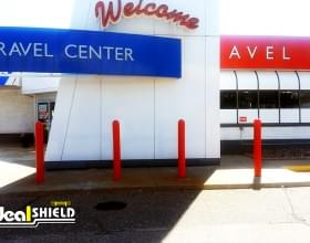 "Ideal Shield's red 1/4"" Bollard Cover guarding a TA Travel Center"