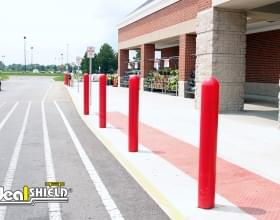 "Ideal Shield's red 1/4"" Bollard Cover guarding a Walmart storefront and sidewalk"