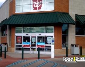 "Ideal Shield's black 1/4"" Bollard Cover guarding Walgreens storefront"