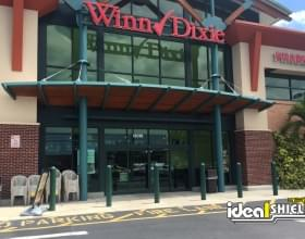 "Ideal Shield's green 1/4"" Bollard Cover guarding Winn Dixie's storefront"