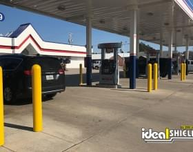 "Ideal Shield's yellow 1/8"" Bollard Cover guarding gas pumps"
