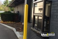 Ideal Shield's yellow Square Bollard Cover used for drive-thru window protection