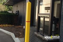 Ideal Shield's yellow Square Bollard Cover with red stripe used for drive-thru window protection
