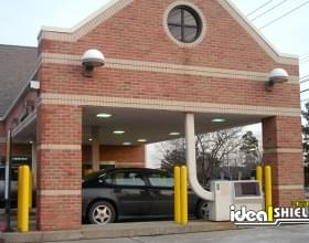 "Ideal Shield's yellow plastic 1/4"" Bollard Covers at a bank drive-thru"