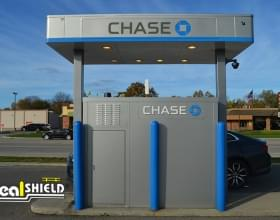 "Ideal Shield's blue plastic 4"" Bollard Covers guarding a Chase Bank ATM drive-thru"