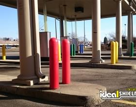 "Ideal Shield's blue, green, yellow, and red plastic 1/4"" Bollard Covers at a bank drive-thru"