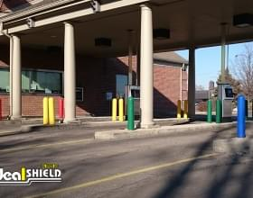 "Ideal Shield's blue, green, yellow and red plastic 1/4"" Bollard Covers at a bank drive-thru"