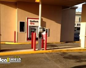 "Ideal Shield's red plastic 1/4"" Bollard Covers at a bank drive-thru"