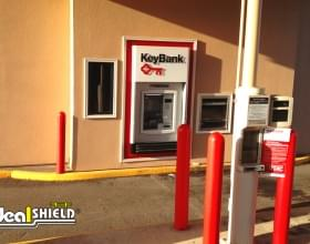 "Ideal Shield's red plastic 1/4"" Bollard Covers at a Key bank drive-thru"