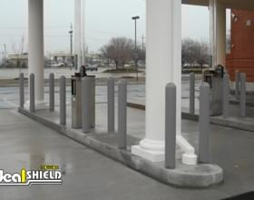 "Ideal Shield's grey plastic 1/4"" Bollard Covers at a PNC bank drive-thru"