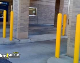"Ideal Shield's yellow plastic 1/4"" Bollard Covers at a PNC bank drive-thru"