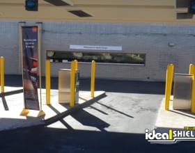 "Ideal Shield's yellow plastic 1/4"" Bollard Covers at a Wells Fargo bank drive-thru"