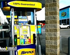 "Ideal Shield's 1/4"" Grey Bollard Cover protecting a Spinx gas pump"