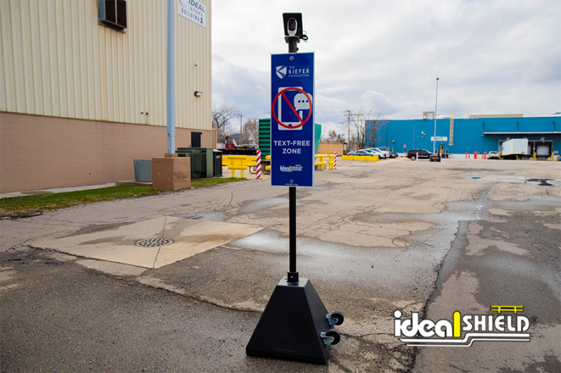 Ideal Shield's Curbside Camera Sign Base System at parking lot entrance