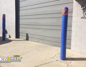 "Ideal Shield's blue plastic 1/4"" Bollard Covers with orange tape used to guard a garage door"