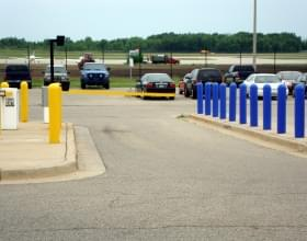 "Multiple colors of Ideal Shield's plastic 1/4"" Bollard Covers used to guard a parking lot entrance and gate"