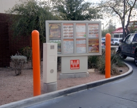 "Ideal Shield's 1/8"" orange bollard covers at a Whataburger drive-thru"