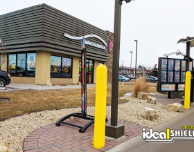 "Ideal Shield's 1/8"" yellow plastic bollard covers guarding a drive-thru at Taco Bell"
