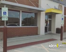 Ideal Shield's custom brown Bollard Sign Systems used for McDonald's handicap accessible storefront parking spots