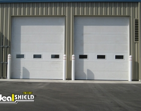 "1/8"" White Bollard Covers Protecting Garage Doors"